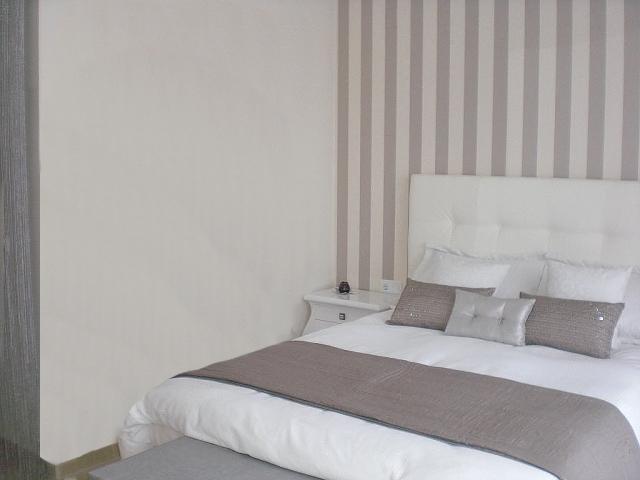 Dormitorio en tonos arena con papel pintado de rayas